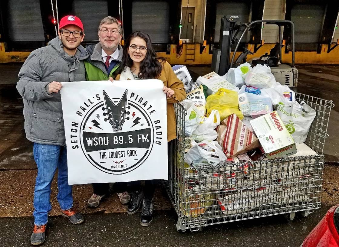 Dalton Allison, Mark Maben and Kali Diamond hold up the WSOU logo in front of their donated food outside of the food bank